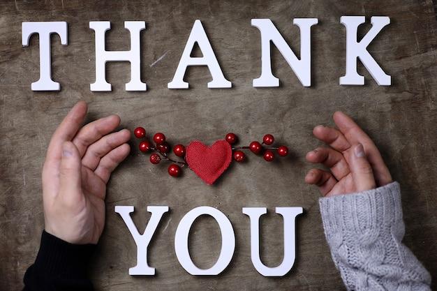 Dankeswort aus weißen holzbuchstaben auf tisch und händen