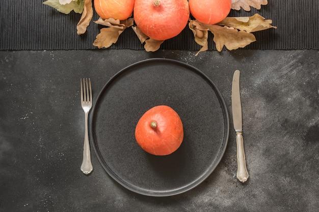 Danksagungs-tages- oder halloween-gedeck mit kürbis auf schwarzer tabelle. ansicht von oben.