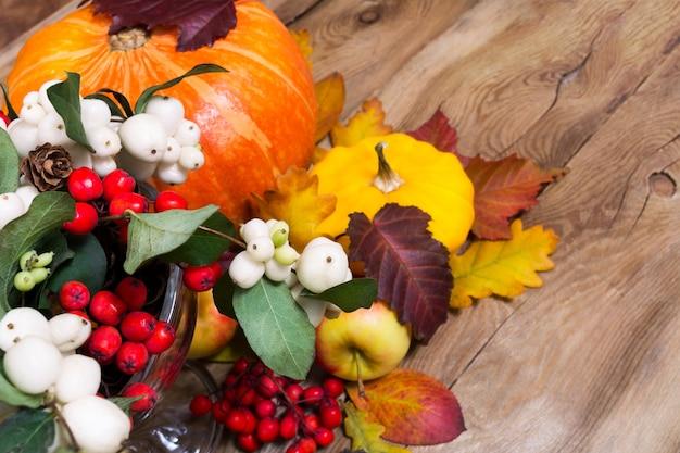 Danksagungshintergrund mit snowberry, kürbis, äpfeln und gelbem kürbis