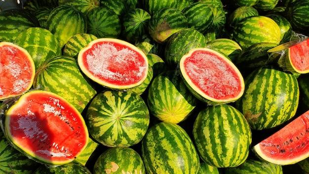 Darauf liegt ein großer haufen grün gestreifter wassermelonen, eine marktbank für einen wassermelonenhändler, geschnittene rote wassermelonen