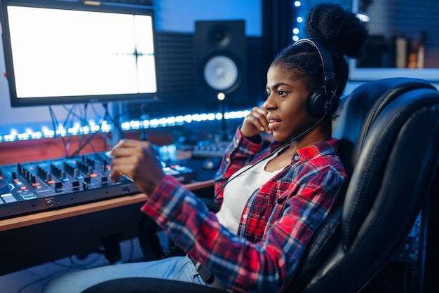 Darstellerin in kopfhörern am monitor im audioaufnahmestudio. toningenieur am mixer, professionelles musikmischen