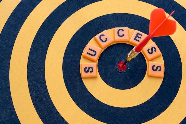 Dart schlägt das bullseye-ziel mit wort erfolg auf der dartscheibe
