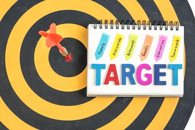 Dart ziel in bullseye mit worten ziel auf dem notebook mit handschrift rechtzeitig erreichbare relevante ziele bildung teamarbeit über dartboard hintergrund, business erfolg konzept