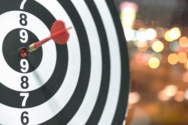 Dart ziel pfeil schlagen auf bullseye mit bokeh hintergrund
