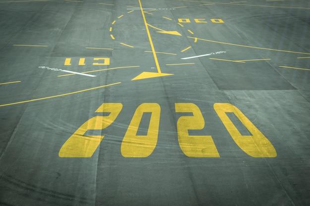 Das 2020-nummernschild auf der landebahn des flughafens zeigt den bevorstehenden neujahrsempfang.