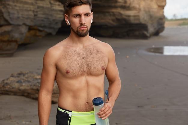 Das abgeschnittene bild eines aktiven joggers oder fitnesstrainers macht pause und trinkt wasser