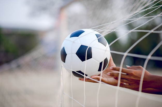 Das abgeschnittene bild von sportlern, die den ball und den fußballplatz fangen.