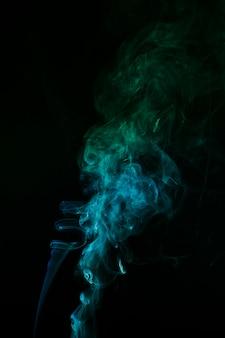 Das abstrakte muster aus blauem und grünem rauch steigt aus einem räucherstäbchen