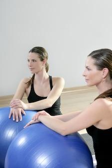 Das aerobic-instruktormädchen, das im spiegel posiert, entspannte sich mit pilates-stabilitätsball