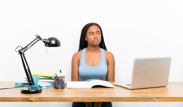 Das afroamerikanerjugendlich-studentenmädchen mit dem langen umsponnenen haar an ihrem arbeitsplatz, der zweifel macht, gestikulieren das schauen der seite