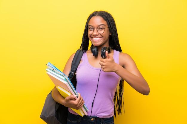Das afroamerikanerjugendlich-studentenmädchen mit dem langen umsponnenen haar über dem lokalisierten gelben wandgeben daumen up geste
