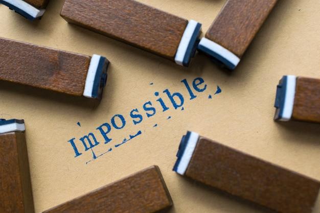 Das alphabetbuchstabewort, das vom stempel unmöglich ist, beschriftet guss auf papier für unmöglichen konzepthintergrund