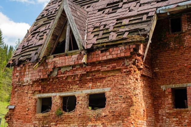 Das alte einstürzende backsteinhaus auf einer hölzernen lichtung