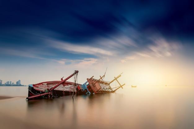 Das alte hölzerne boot des fischers des fischers, der auf dem strand und dem sonnenunterganghimmel geparkt wird, ist schön.