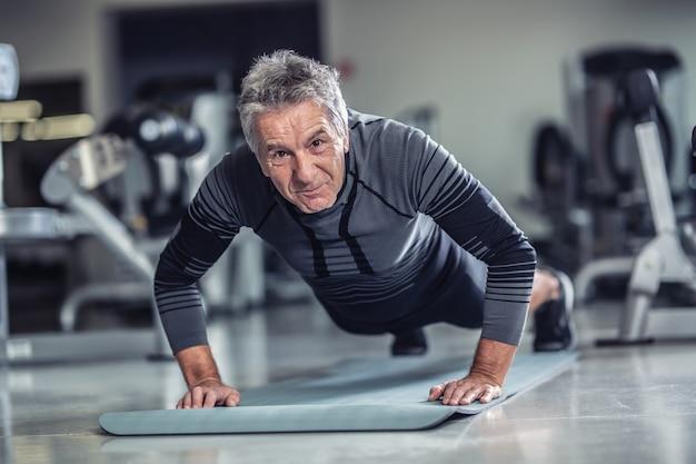 Das alter ist nur eine zahl für einen mann mit grauen haaren, der liegestütze in einem fitnessstudio macht.