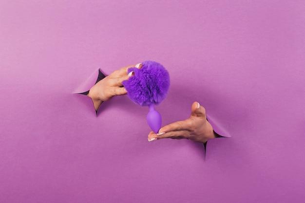 Das anal sexspielzeug auf einem rosa hintergrund in den händen einer frau
