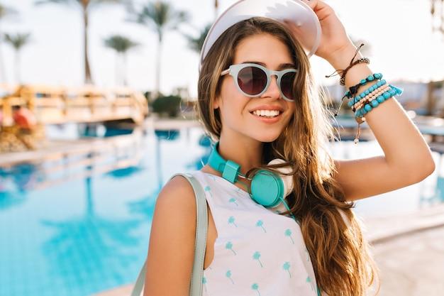 Das anmutige mädchen mit sonnenbrille und hut und trendigem rucksack kam zum pool, um sich auf dem bett zu sonnen