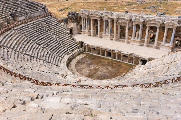 Das antike steintheater und das griechische amphitheater in hierapolis bei pamukkale in der türkei gehören heute zum unesco-weltkulturerbe und blicken von oben auf die sitze