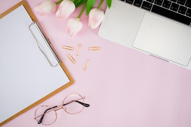 Das arbeitszubehör der frauen liegt flach auf rosa pastellrosapapier. bilder aus der draufsicht einfacher stil mit platz für texteingabe.