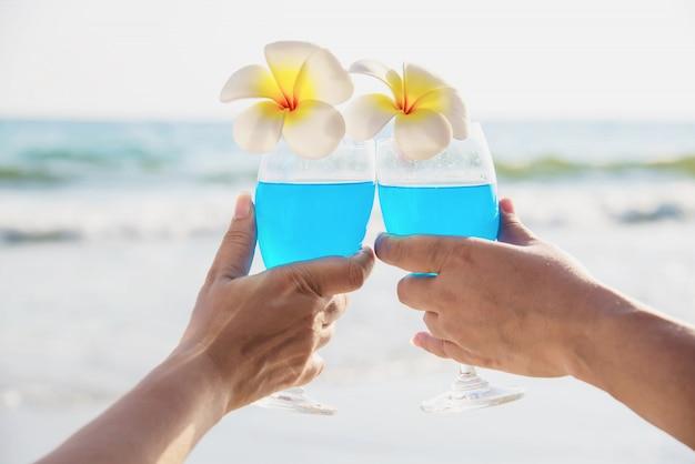 Das asiatische ccouple, das cocktailglasdekoration mit plumeriablume mit wellenseestrand hält - glücklich entspannen sie sich feierferien im seenaturkonzept