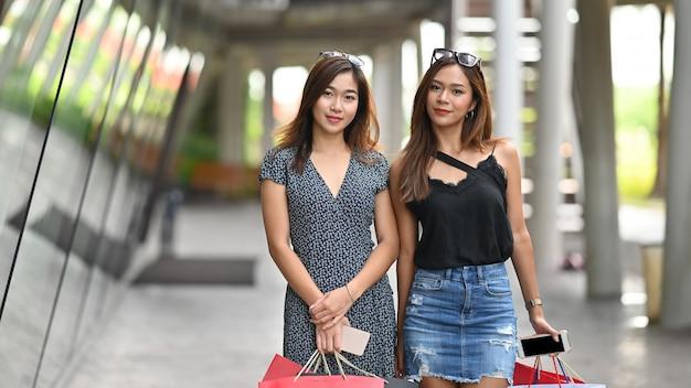 Das asiatische einkaufen zusammen mit porträt schoss mit einkaufstasche auf händen.