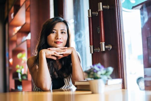 Das asiatische frauenlächeln des porträts entspannen sich im kaffeestubecafé