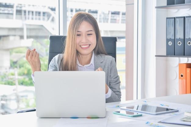 Das asiatische geschäft, das mit laptop arbeitet und den erfolg hat, der arme anhebt, erhalten nach gute nachrichten