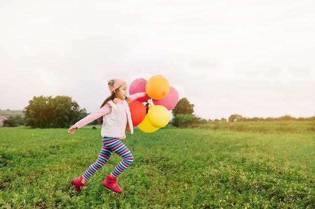 Das asiatische glückliche kind, das mit buntem spielzeug läuft, steigt draußen im ballon auf