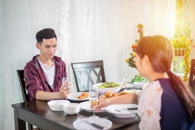 Das asiatische junge paar, das einen romantischen abendessenabend genießt, trinkt beim am esstisch auf der küche zusammen sitzen