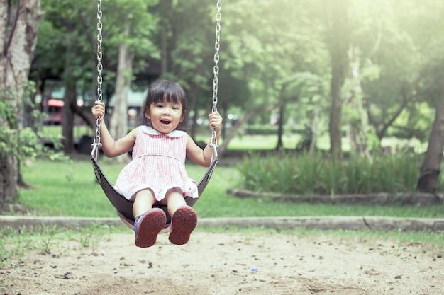 Das asiatische kind, das spaß hat, um zu spielen, schwingen im spielplatz im weinlesefarbton