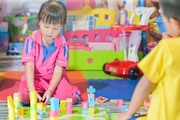 Das asiatische kind des kleinen mädchens, das in den raumspielwaren für kinder spielt, entwickeln sich in der vorschule, alias kindergarten