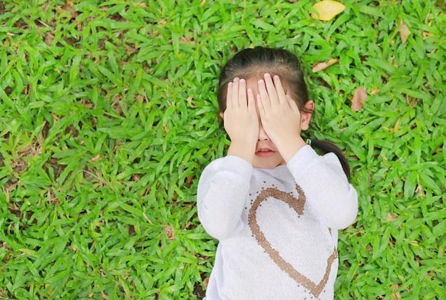 Das asiatische kindermädchen, das auf rasen des grünen grases liegt, schloss ihre augen mit ihren händen