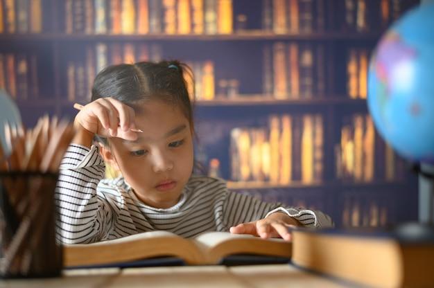 Das asiatische kindermädchen, das fleißig ist, sitzt zuhause an einem schreibtisch. kind lernt zu hause