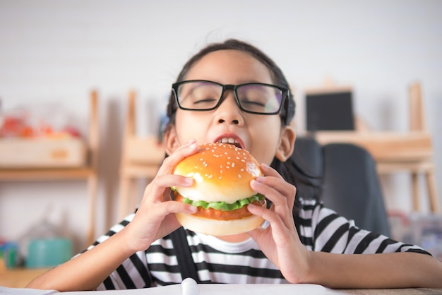 Das asiatische kleine mädchen, das hamburger auf holztisch isst, wählen flache schärfentiefe des fokus aus