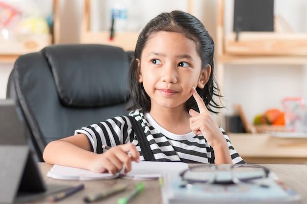 Das asiatische kleine mädchen, das hausarbeit auf holztisch tut, wählen flache schärfentiefe des fokus aus