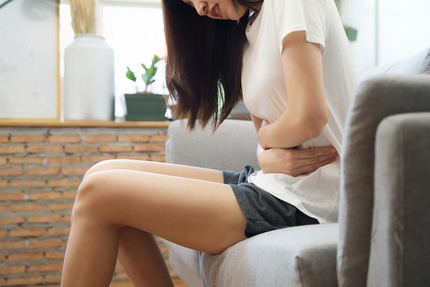 Das asiatische mädchen, das periode hat, sitzt auf sofa und fühlt sich auf ihrem magen schmerzlich.