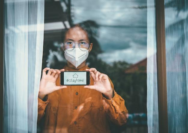 Das asiatische mädchen mit brille, das eine maske trägt und das telefon mit der aufschrift #stayhome hält, ist es gelangweilt, die krankheit allein zu hause festhalten und behandeln zu müssen. konzept heimquarantäne, prävention covid-19