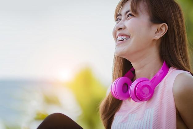 Das asien-frauensitzen, das musik hört, entspannen sich nach übung