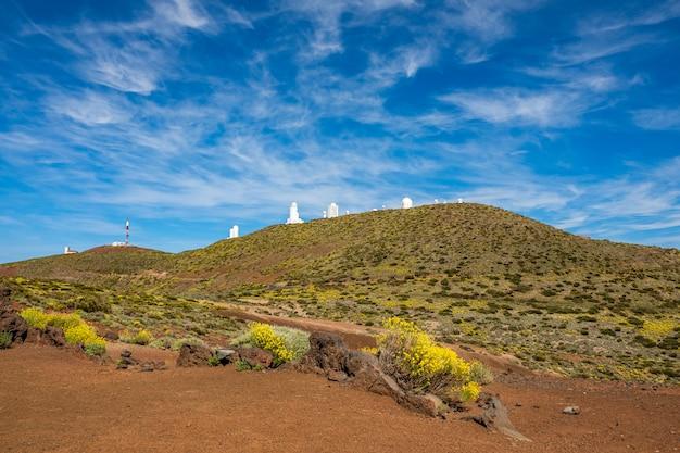 Das astronomische observatorium von teide taucht hinter einem hügel auf