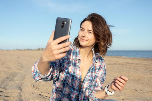 Das atmosphärische lebensstilfoto der jungen schönen dunkelhaarigen frau im hemd und in den jeans im freien macht selfie am strand