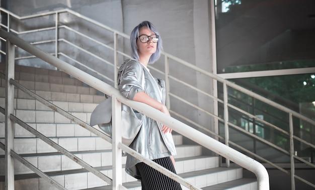 Das attraktive mädchen im weltraumstil in einem regenmantel aus silbernem stoff geht die treppe hinunter.