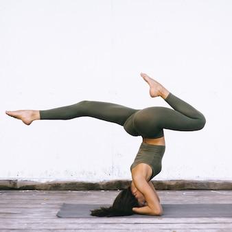 Das attraktive modell, das yoga tut, trainiert auf weißem hintergrund in der sexuellen kleidung