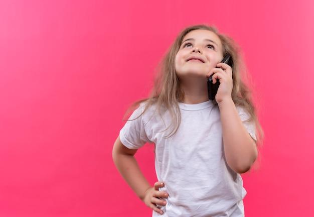 Das aufschauen des kleinen schulmädchens, das weißes t-shirt trägt, spricht am telefon, legte ihre hand auf hüfte auf lokalisiertem rosa hintergrund