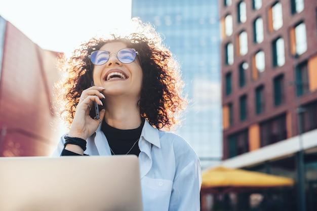 Das aufschauen einer person mit lockigem haar jubelt draußen, während sie am computer arbeitet und telefoniert