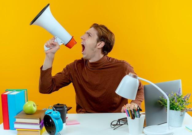 Das aufschauen eines wütenden jungen studentenjungen, der mit schulwerkzeugen am schreibtisch sitzt, spricht über lautsprecher