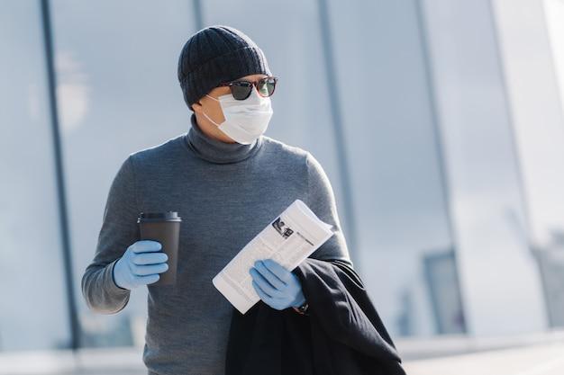 Das außenbild eines männlichen arbeiters kehrt von der arbeit nach hause zurück, dreht den kopf zur seite, trinkt kaffee zum mitnehmen, hält zeitung, trägt eine medizinisch sterile maske und gummihandschuhe und verhindert die ausbreitung des coronavirus. infektiöses virus