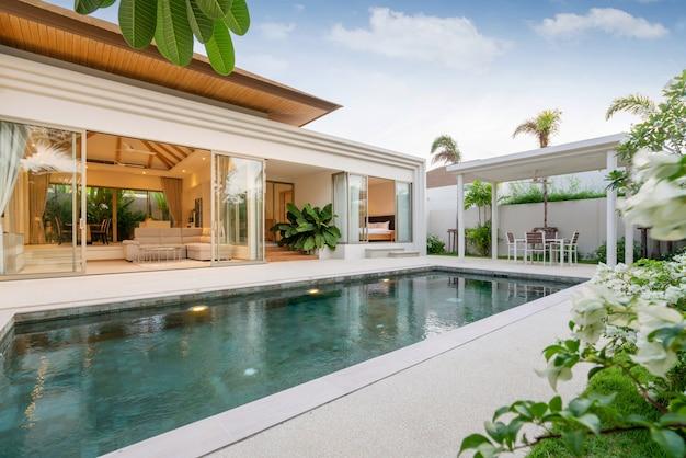 Das außendesign der poolvilla, des hauses und des hauses verfügt über einen infinity-pool und einen garten