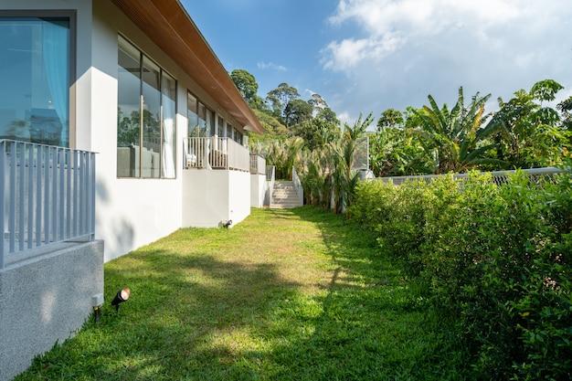 Das außendesign der villa, des hauses und des hauses bietet eine landschaft und einen grünen garten neben dem haus
