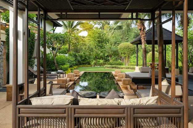 Das außendesign von haus, haus und villa umfasst einen swimmingpool, ein sofakissen, ein tagesbett, einen pavillon und einen garten