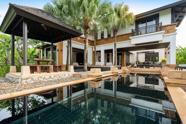 Das außendesign von haus, haus und villa umfasst einen swimmingpool, einen pavillon und ein gebäude
